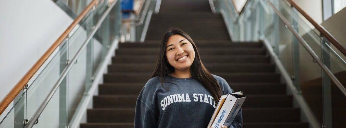 Student holding textbooks and wearing an SSU sweatshirt