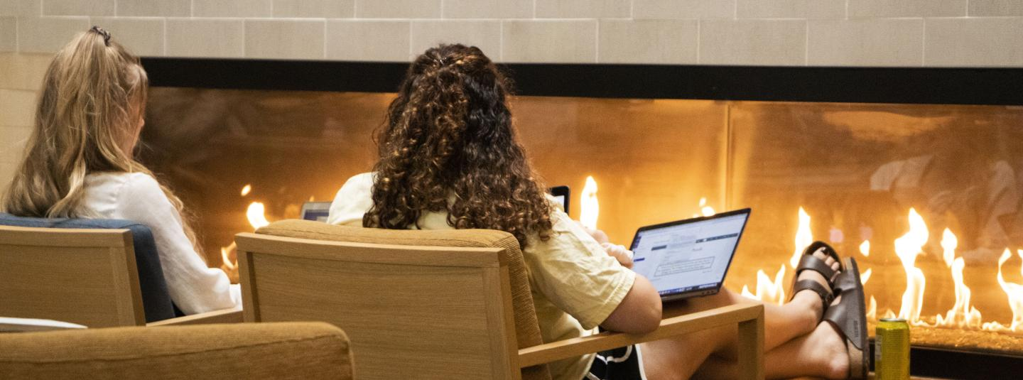 Student on computer in front of fireplace in Student Center